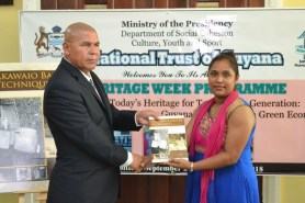 Minister of Social Cohesion, Dr. George Norton receives first copy of Akawaio Basketry Techniques from Chief Executive Officer (CEO) of the National Trust of Guyana Nirvana Persaud.