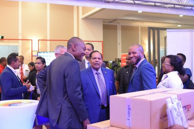 Prime Minister Moses Nagamootoo, Minister of Business Dominic Gaskin and GO-INVEST CEO, Owen Verwey engaging representatives at the Caribbean Airlines booth..