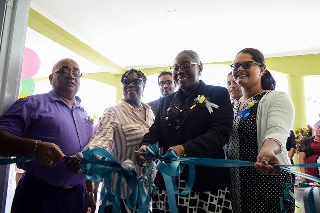 Senior Project Officer of the Ministry of Communities, Karen Roopchand, Regional Executive Officer (REO), Denis Jaikaran and Regional Education Officer, Annesta Douglas during the symbolic cutting of the ribbon to commission the education complex.