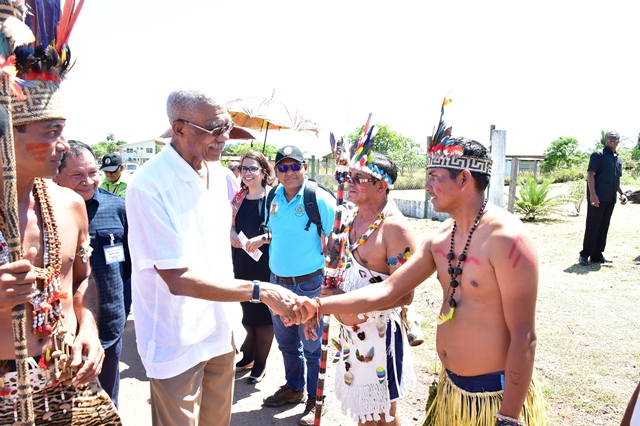 President David Granger greets a resident of St. Ignatius upon his arrival at the village for the Rupununi Heritage celebrations 2018. Also, in photograph are Chairman of the National Toshaos' Council Nicholas Fredericks (left) and Brazilian Vice-Consul, Ms. Lisa Mary Sousa Dos Reis.