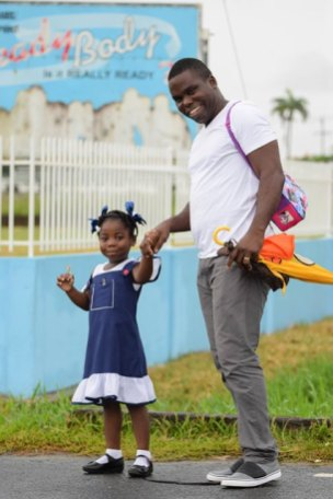 Marwin Layne and his daughter smile as they make their way to school.