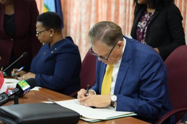 Minister Volda Lawrence and Dr. Gernot Grimm signing the MoU on behalf of their respective nations