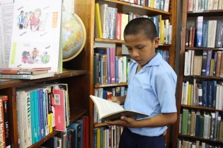 One of the students perusing a book from the shelves of the National Library.