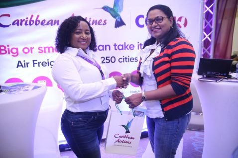 Coordinator of GuyTIE, Tameca Singh collects a token from a Caribbean Airlines representative