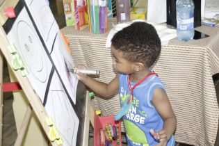 A young lad improving his painting skills at the literacy day activities