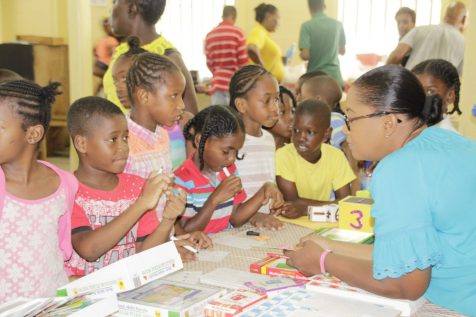 A volunteer interacting with children of the Albouystown/Charlestown community today