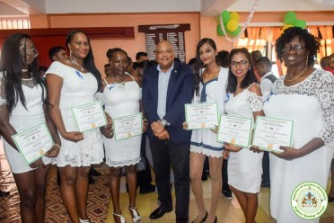 Minister of Natural Resources, Hon. Raphael Trotman among some female graduates.