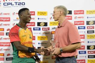 Sherfane Rutherford receiving his Man of the Match trophy from ExxonMobil Country Manager, Rod Henson.