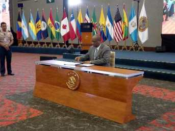 Minister Harmon signs the Declaration of Cancun.