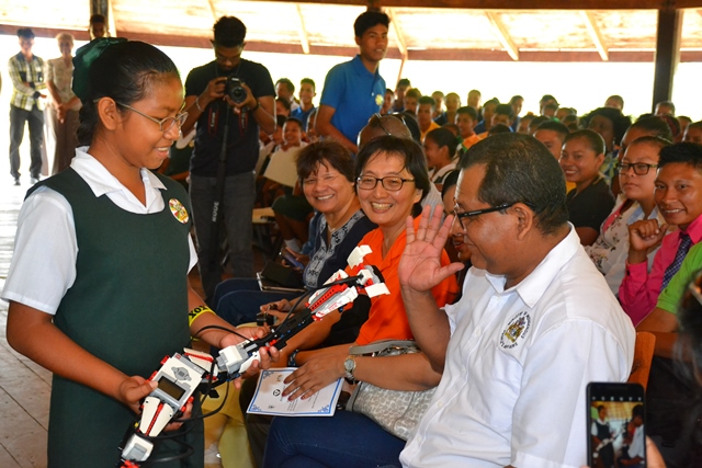 Canadian High Commissioner to Guyana, Ms. Lilian Chatterjee, UNDP Resident Representative to Guyana, Ms. Mikiko Tanaka and a representative of the Ministry of Indigenous People's Affairs smile as this student of the Annai Primary School showcases a robot.
