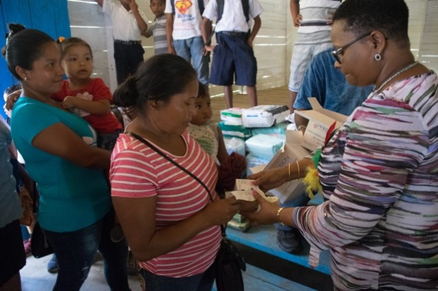 Minister of Public Health, Volda Lawrence distributing first aid supplies to children and residents during her recent visit.