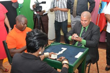 Minister of Social Cohesion, Dr. George Norton [right] participating in a ceremonial game with President of the Guyana National Domino Federation, Faye Joseph and General Secretary of the World Council of Dominoes Federation Championships, Gregory Blenman