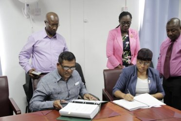 Mr. Brian Tiwarie signing the contract documents along with Permanent Secretary within the Ministry of Education, Ms. Adele Clarke.