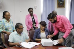 Mr. Roy Bassoo signing the contract documents along with Permanent Secretary within the Ministry of Education, Ms. Adele Clarke.