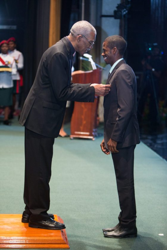 President David Granger conferring the Medal of Service on National Athlete, Cleveland Forde