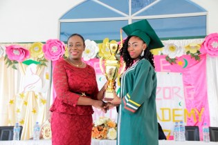 Minister of Education, Hon. Nicolette Henry presenting top CSEC student, Kaecia Winter with her trophy.