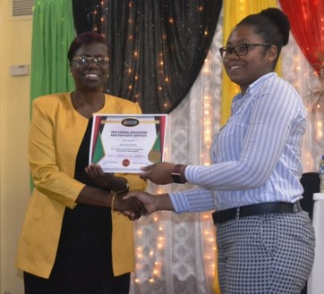 Ms. Sheriyln Innis receiving her certificate from the Permanent Secretary
