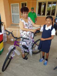 Minister of Social Protection, Ms. Amna Ally, presents a bicycle to a student from the Crabwood Creek Community