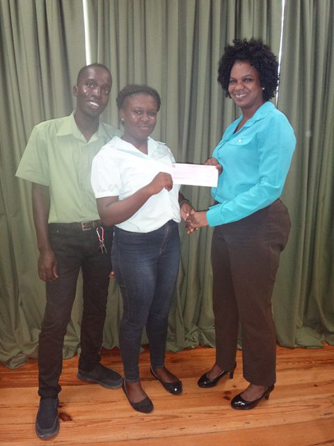 Mr and Mrs. Sinclair receiving their cheque from Assistant Director of Youth, Ms. Leslyn Boyce.