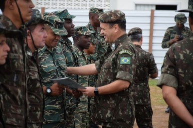 Brigadier General, 2nd Engineering Group, Brazilian Army, Marcus Fontoura de Melo hands over a certificate to one of the officers from the Guyana Defence Force.