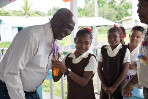 Minister within the Ministry of Social Protection, with responsibility for Labour, Keith Scott, being welcomed by primary school children