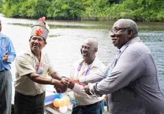 Minister within the Ministry of Social Protection, with responsibly for Labour, Keith Scott and Board Chairman of Board of Industrial Training (BIT), Clinton Williams hand keys for the boat to the Toshao Sherman Lyte
