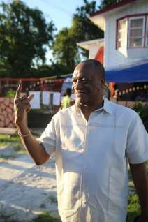 Minister of State, Joseph Harmon showing his inked finger after casting his vote