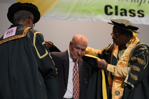 Businessman Yesu Persaud being robed by Vice Chancellor of UG, Professor Ivelaw Griffith before being conferred his Doctor of Letters from Chancellor of UG, Professor Eon Harris.
