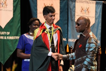 Acting Prime Minister and Minister of Foreign Affairs, Carl Greenidge, congratulates Mohameed Baksh after presenting him with the Prime Minister's Medal.