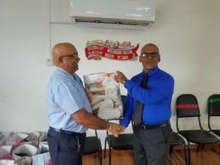 Outgoing REO Denis Jaikaran presents a Christmas hamper to Vice Chairman Sheik Ayube