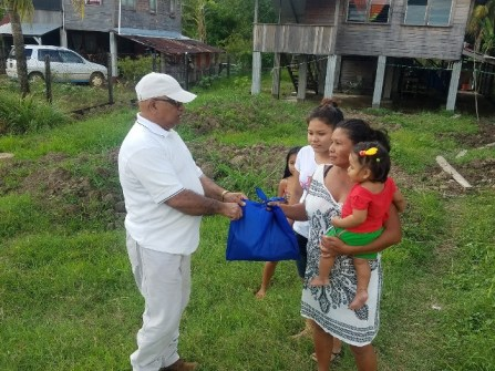 Family receiving cleaning agents from REO Jaikaran.