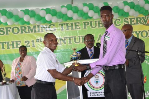 Audlie Waterton receiving one of his two awards from Permanent Secretary (ag) Andrew Grannt