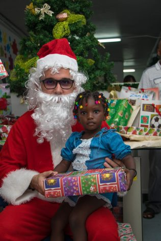 Another child receiving her gift from Santa Claus