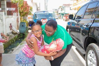 Minister Simona Broomes presents one of the little girls with her gift.