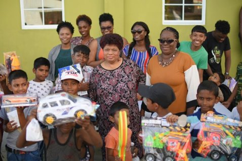 Minister of Social Protection, Amna Ally with some of the children who received gifts as part of the Christmas Toy Drive.