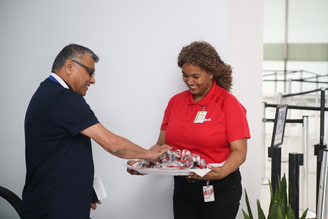 The staff of the Guyana Tourism Authority welcoming incoming passengers at the Cheddi Jagan International Airport (CJIA) with black cake.