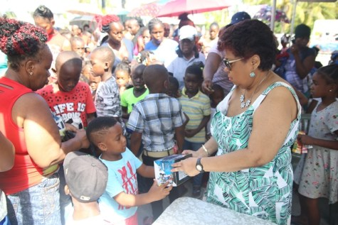 Minister of Social Protection, Amna Ally distributing toys to the children of Buxton.