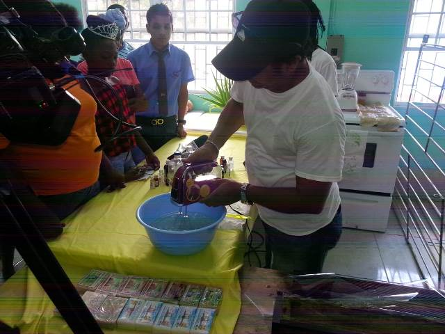 Coconut farmer and agro-processor, Owen DeSouza showing students the steps to make coconut oil.