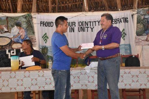 Minister of Indigenous Peoples' Affairs, Sydney Allicock handing over a cheque to Toshao of Quiko, Ronald Ignatius