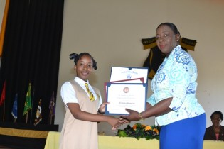 Minister of Education Dr. Nicolette Henry presenting Queen's College student twelve-year-old Nathalia Squires, her awards.