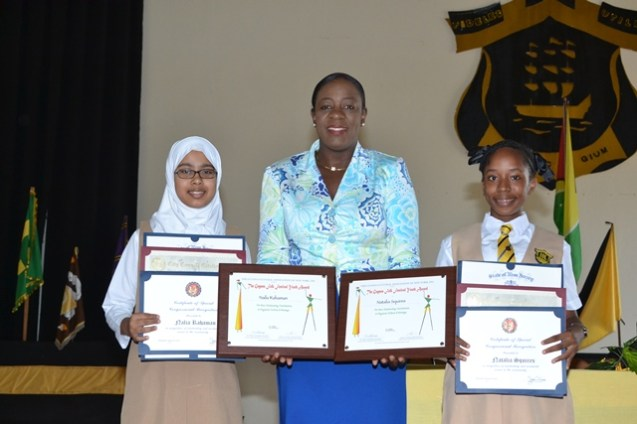 (left to right) Eleven-year-old Naila Rahaman, Minister of Education Dr. Nicolette Henry along with twelve-year-old Nathalia Squires presenting their awards.