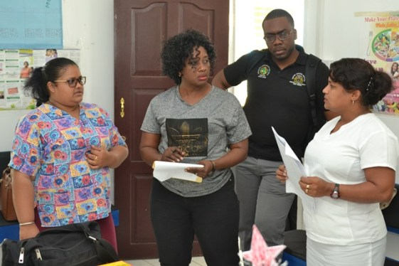 Dr. Kay Shako and Dr. Horace Cox [centre] interacts with staff of the Agatash Health Post.