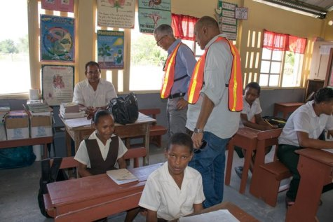 Minister of Natural Resources, Raphael Trotman and Minister of Business, Dominic Gaskin interacting with a teacher and student of the Sand Hills Primary school.