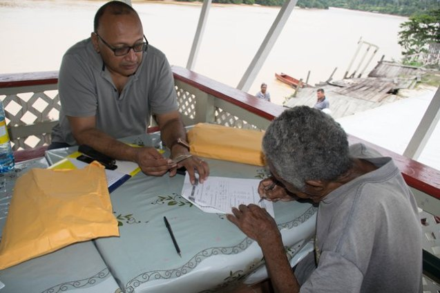 A representative from the Ministry of Social Protection advising a senior citizen of his social benefits.