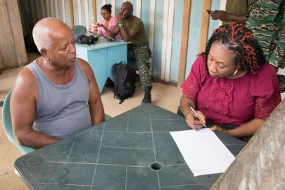 General Register's Office official giving assistance to a resident in Arau, Region 7.