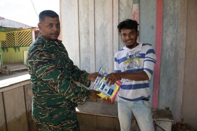 Civil Defence Commission, Operations Officer Lieutenant Lakshman Persaud handing over a hygiene kit to a resident in Arau.
