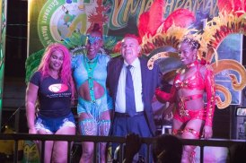 Minister of Social Cohesion, Dr. George Norton accompanied by the ministry's revelers and costume designer.