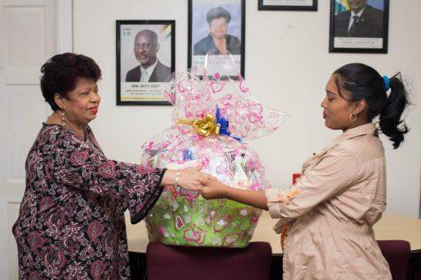 Minister of Social Protection presenting the hamper to Domestic violence Survivor victim, Natasha Houston