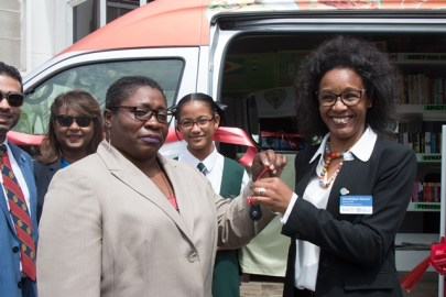 From right to left are Rotary District Governor, Dominique Venre handing over the key of the Bookmobile to Deputy Chief Librarian, Nadine Moore.
