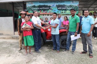 Minister of Indigenous Peoples' Affairs, Sydney Allicock handing over the keys to the ATV to Deputy Toshao of Rukumuta Village, Kim Binto in the presence of Region Nine's Regional Executive Officer, Carl Parker and residents of Rukumuta Village.
